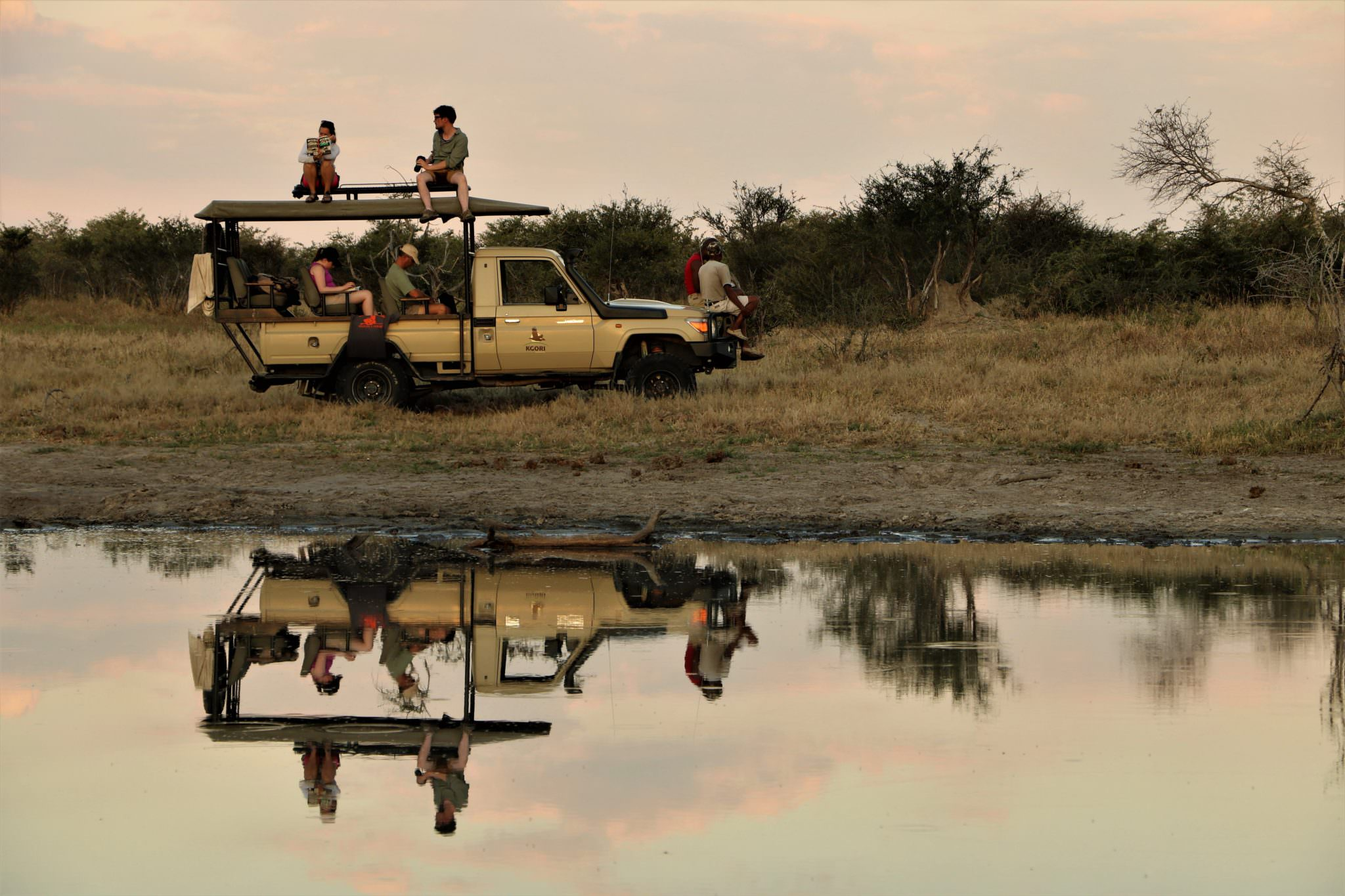 A group of conservation volunteers sitting on top of a jeep next to a lake in the African bush