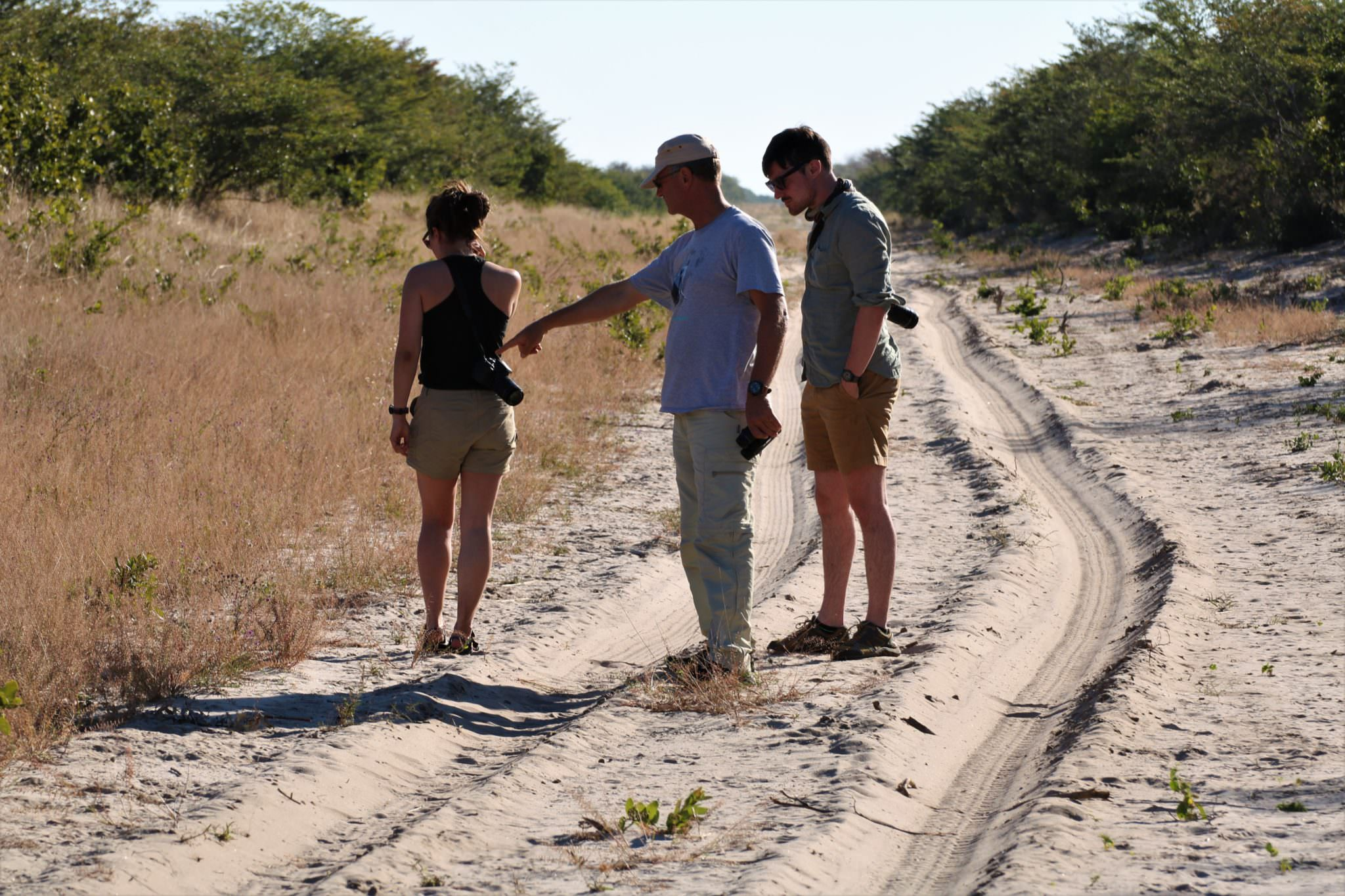 Conservation volunteers standing on a dirt track identifying tracks conducting a spoor survey
